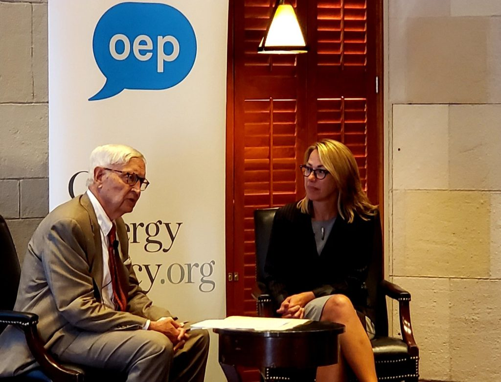 Dale Bryk of Governor Cuomo's office is seated in a chair on the right, and Bob Semple of the New York Times is seated in a chair to the left of her. He asks her questions about energy policy. A banner with the OurEnergyPolicy logo is behind them.